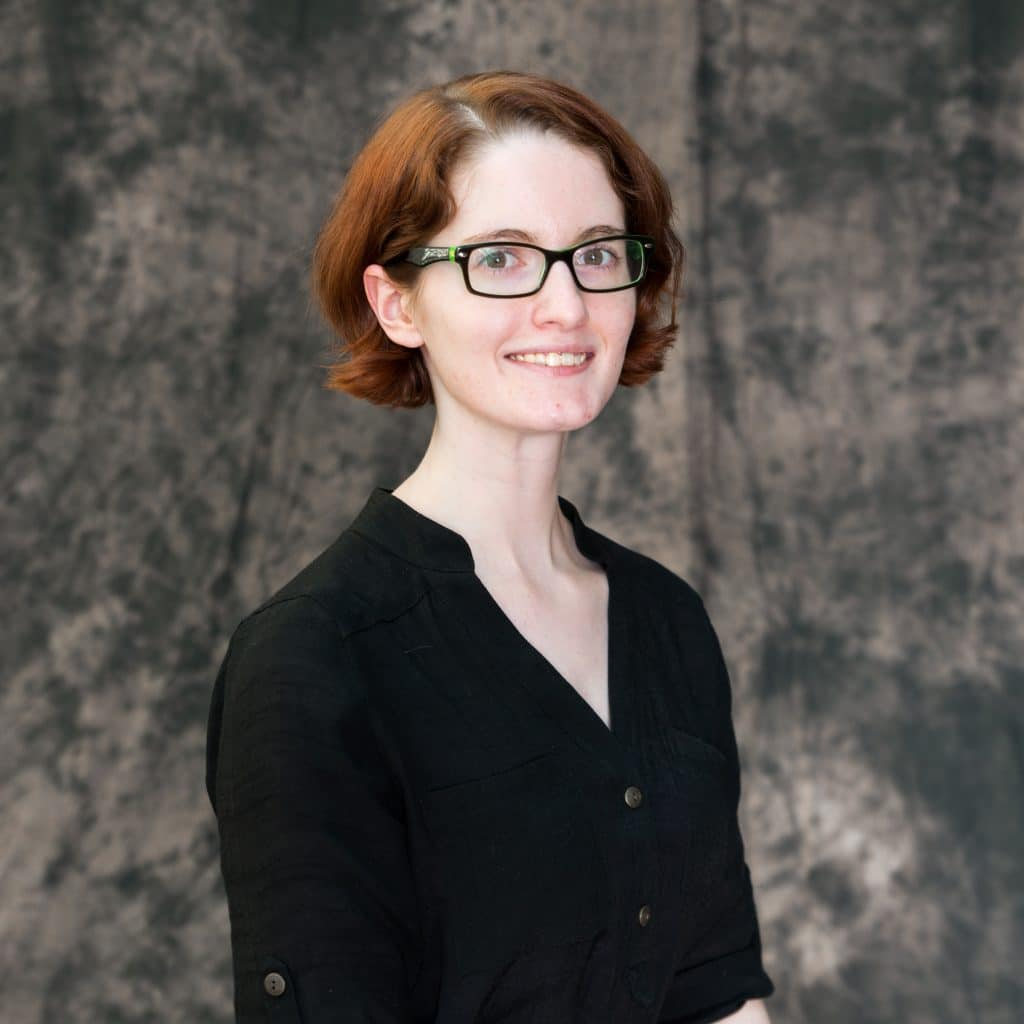 Upper body shot of Erin Howard smiling at the camera with a gray neutral background. They have chin-length red hair. They are wearing black-framed glasses and a black button-up shirt.
