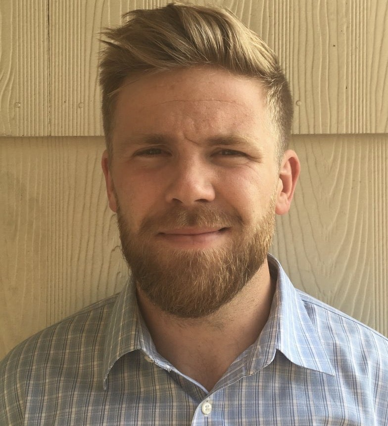 A headshot of Tripp smiling. He has short blonde hair and a beard and is wearing a light blue checkered button-up.