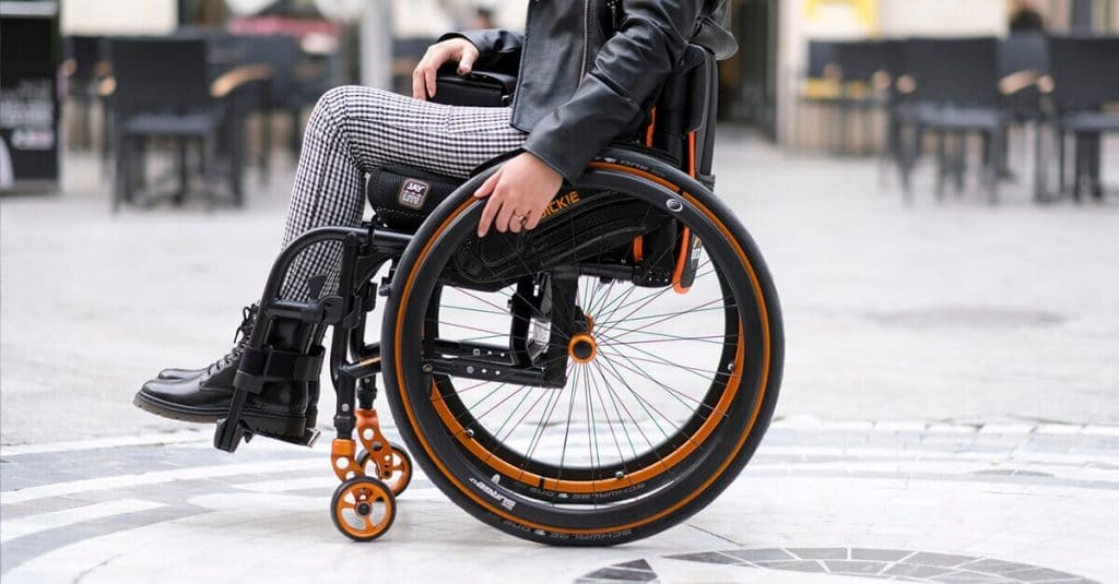 Photo of a wheelchair with a with a chair user. The picture is cropped to focus on the wheels and crops out majority of the wheelchair users upper body. Woman in wearing checkered pants and a leather jacket