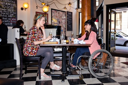 Two women sitting in a restaurant. The woman on the right is in a wheelchair wearing a pink top and blue jeans.